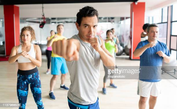 young handsome coach leading a boxing class at the gym - hispanolistic stock photos and pictures