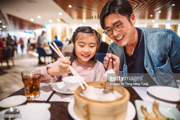 young handsome dad enjoying steamed chinese dumplings with his lovely little daughter in chinese restaurant - genderblend stock pictures, royalty-free photos & images