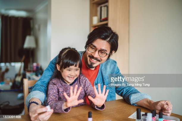 young handsome dad polishing his daughter's fingernails at home joyfully - human finger stock pictures, royalty-free photos & images