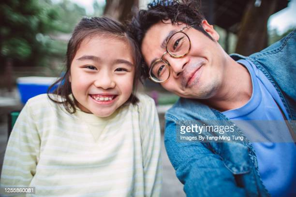 young handsome dad taking selfies joyfully with her lovely daughter while enjoying barbecue picnic in country park - genderblend stock pictures, royalty-free photos & images