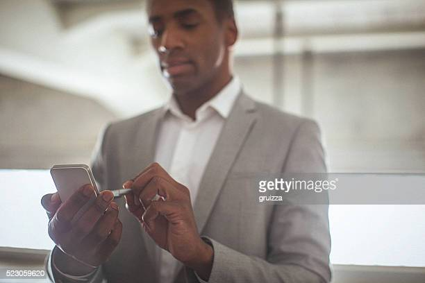 Young handsome entrepreneur typing text message on his smartphon