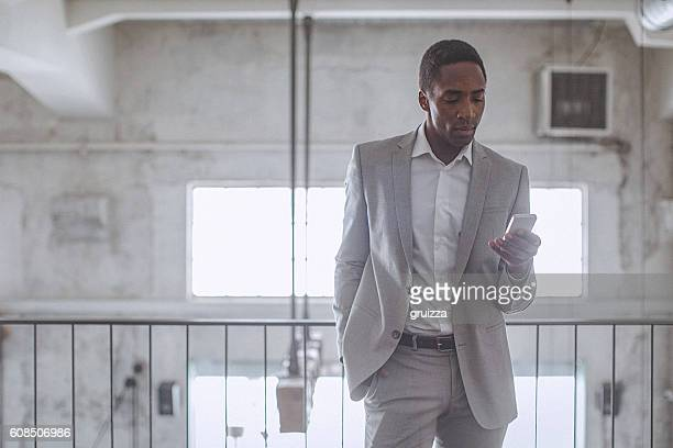 Young handsome entrepreneur typing text message on his smartphone
