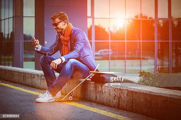 Jeune bel homme d'affaires à l'aide de smartphone dans l'environnement urbain