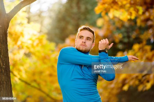 young handsome hipster runner stretching outside in autumn natur - natur stock pictures, royalty-free photos & images