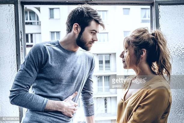 young handsome man and beautiful woman looking eachother at window