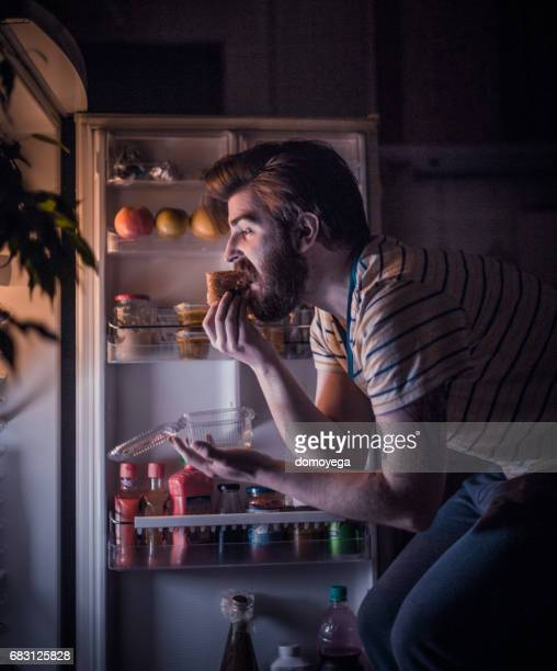 Young handsome man eating late night in front of the refrigerator