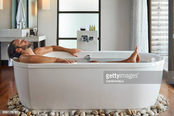 young handsome man enjoying in the bathtub