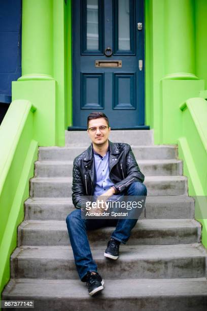 young handsome man in glasses sitting on a steps infront of a green house - green coat stock pictures, royalty-free photos & images