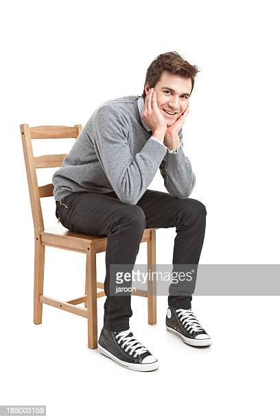 young handsome man in grey sweater sitting on chair - sitting stock pictures, royalty-free photos & images