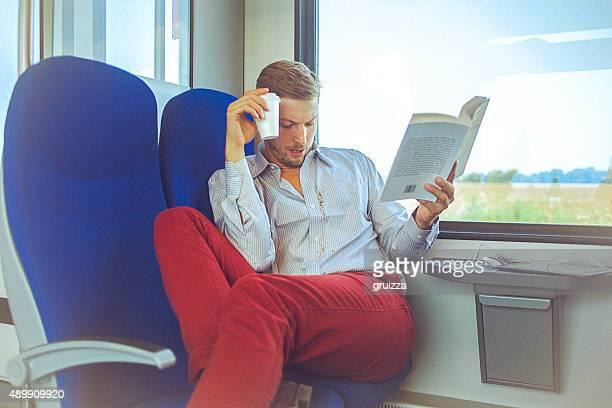 Junger hübscher Mann im Zug Verschütten Kaffee auf dem shirt