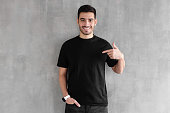 Young handsome man isolated on gray textured wall, smiling while pointing with index finger to black t-shirt, copyspace for advertising