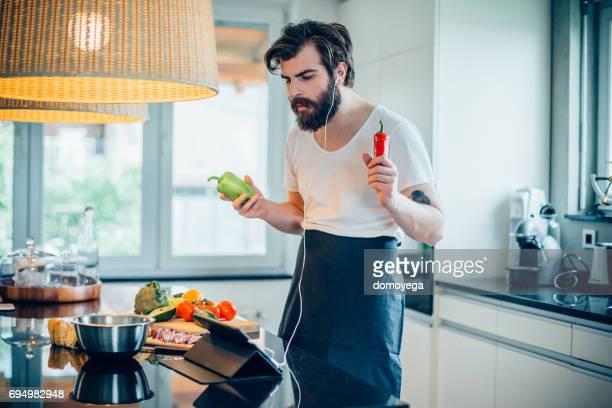 Schönen jungen Mann Musik hören und gesunde Avocado Mahlzeit kochen