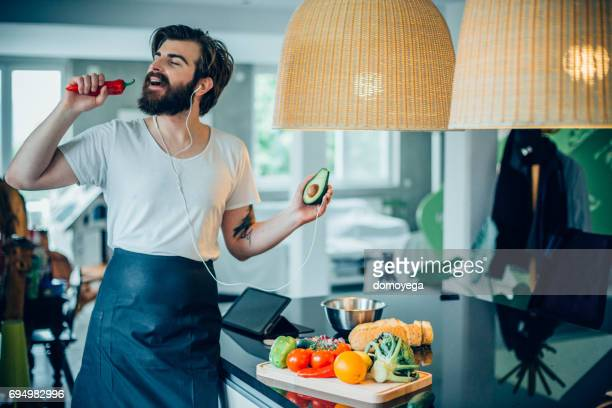 young handsome man listening music and cooking healthy avocado meal - cantare foto e immagini stock