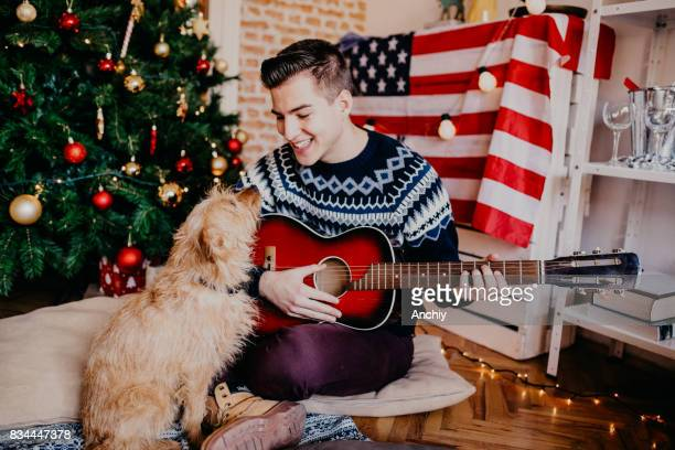 Jonge knappe man gitaarspelen aan zijn hond voor een kerstboom.