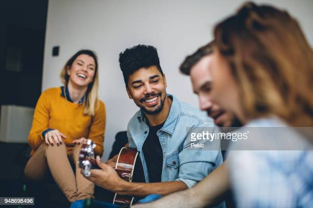 young handsome man playing guitar to his friends - plucking an instrument stock pictures, royalty-free photos & images