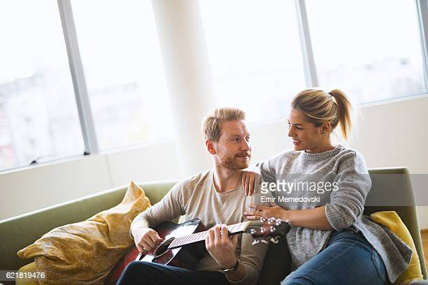 Young handsome man playing guitar to his girlfriend.