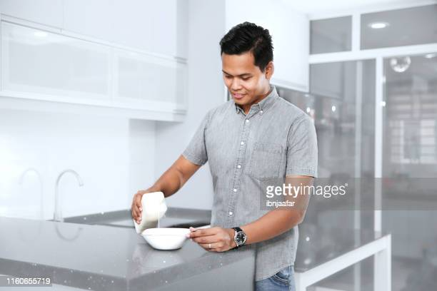 young handsome man preparing food in kitchen - ibnjaafar stock photos and pictures