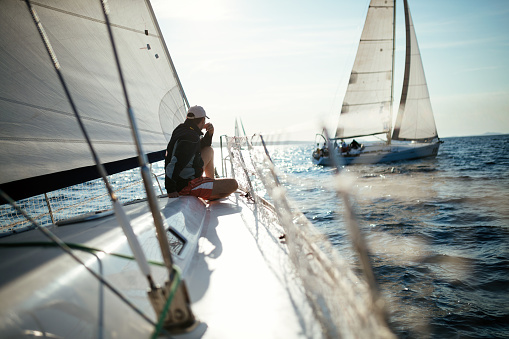 Young handsome man relaxing on his sailboat 944496600