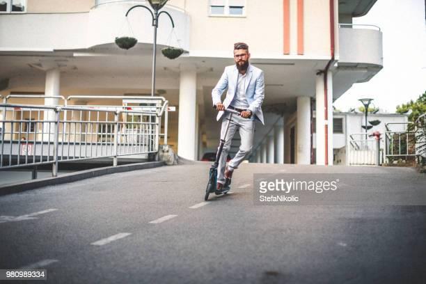 若いハンサムな男乗馬プッシュ スクーター - 気が若い ストックフォトと画像