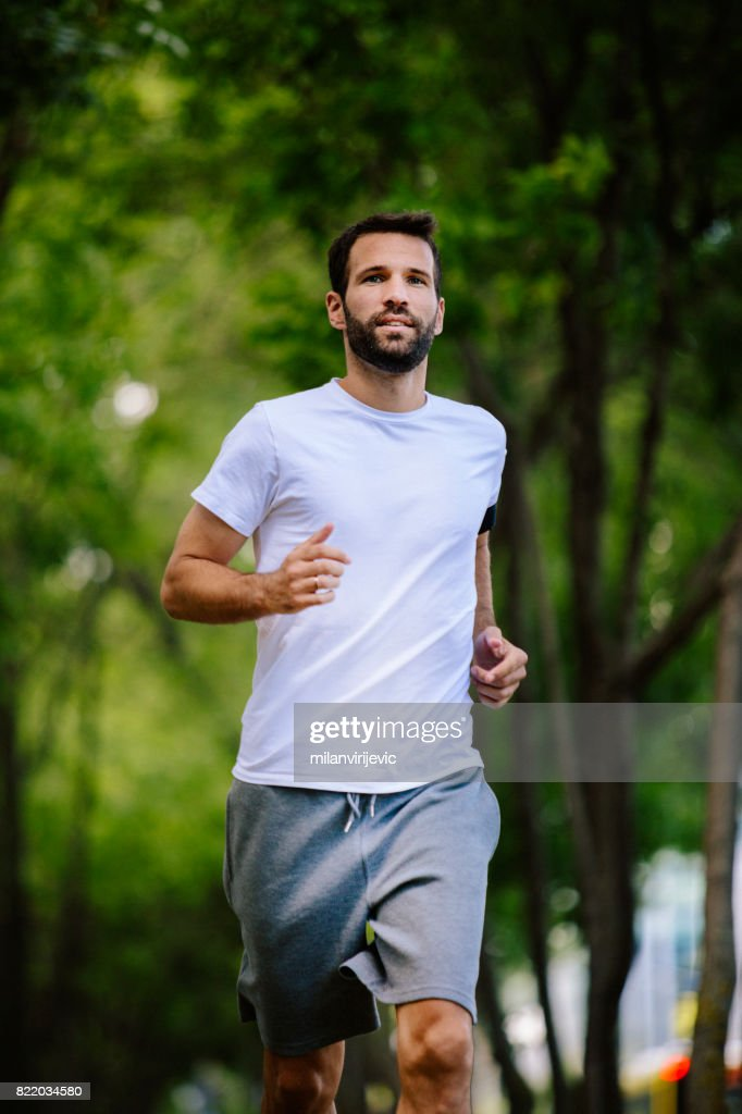 Young handsome man running in nature : Stock Photo