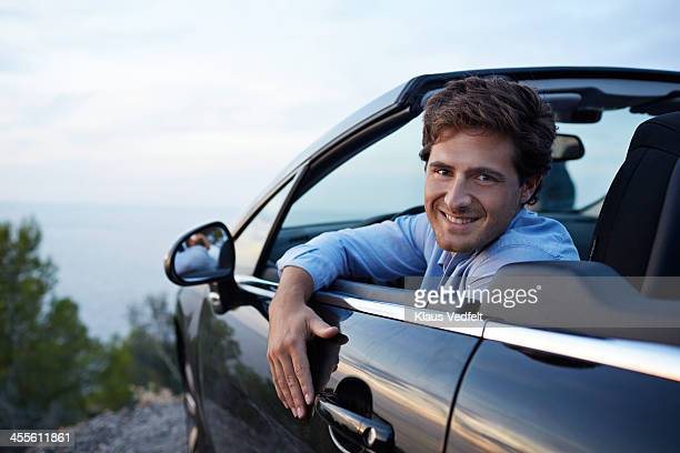 young handsome man sitting in car - klaus vedfelt mallorca stock pictures, royalty-free photos & images