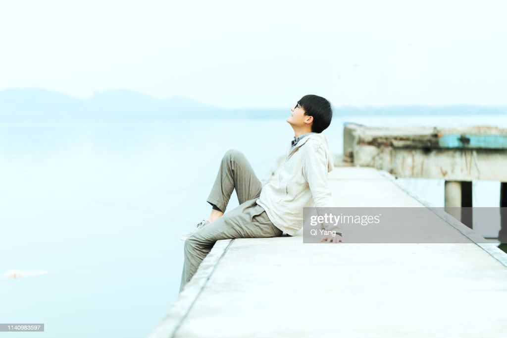 Young handsome man sitting on pier : Stock Photo