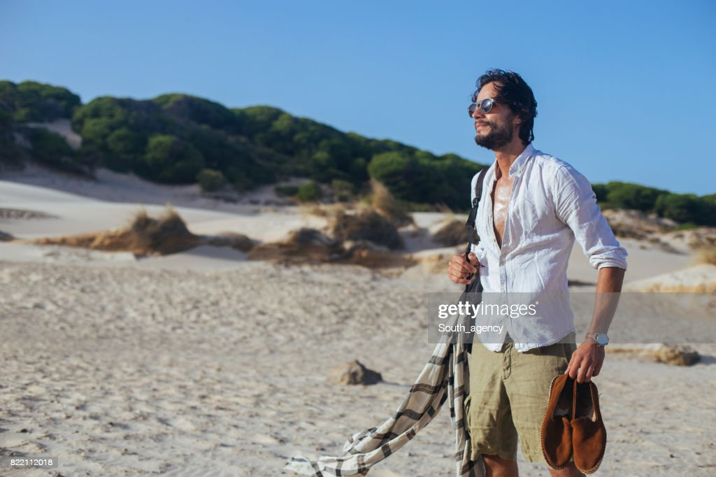 Young handsome man standing at the beach : Stock Photo