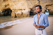 young handsome man standing at beach