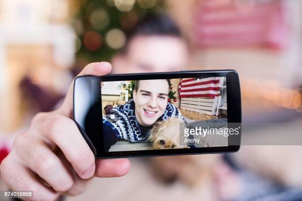Hombre guapo joven tomando un selfie con su perro delante de un árbol de Navidad. Bandera americana