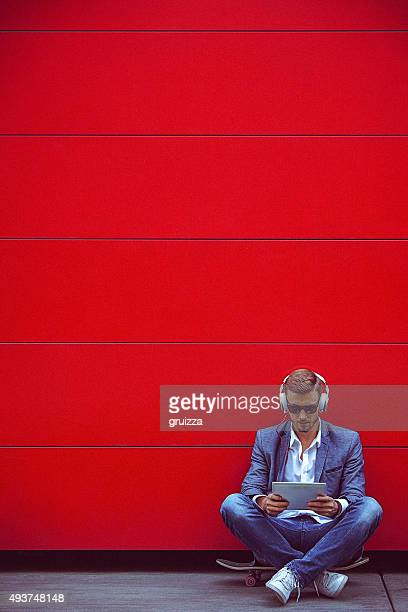 young handsome man using digital tablet beside the red wall - funky stock pictures, royalty-free photos & images