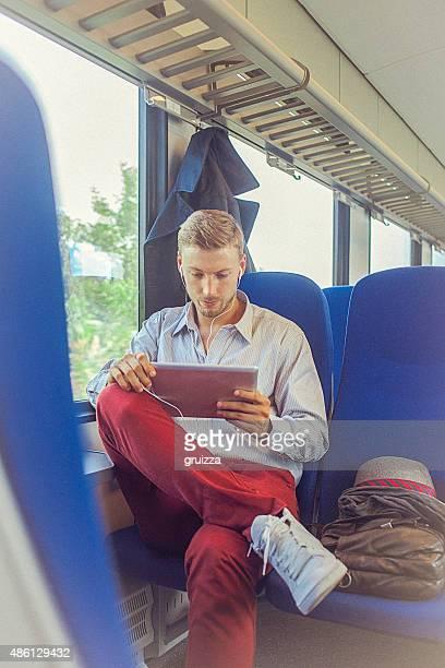 Hombre atractivo joven usando tableta digital mientras que he viajado para trabajo