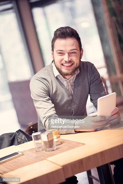 Young Handsome Man using his Digital Tablet in Coffee Shop