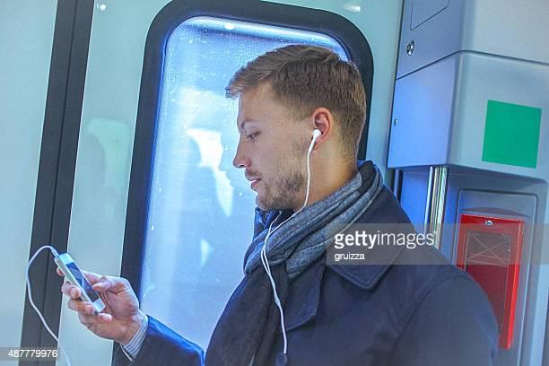 Junger gut aussehender Mann, mit Smartphone während der Fahrt zur Arbeit