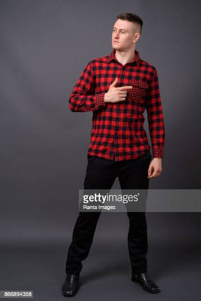 young handsome man wearing red checked shirt against gray background - checked shirt stock photos and pictures