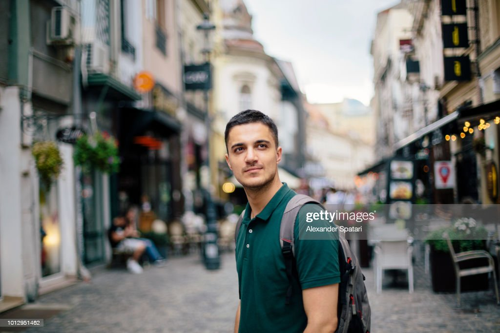 Young handsome man with backpack on the street of the old town : Stock Photo