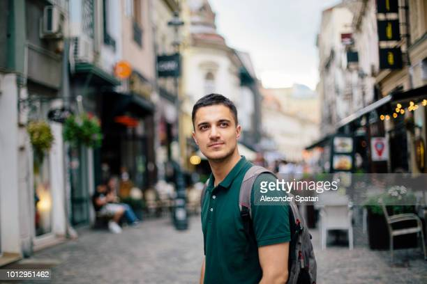 young handsome man with backpack on the street of the old town - bucharest stock pictures, royalty-free photos & images