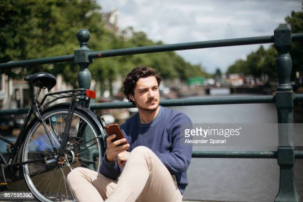 Young handsome man with mobile phone sitting on the bridge across the canal, Amsterdam, Netherlands