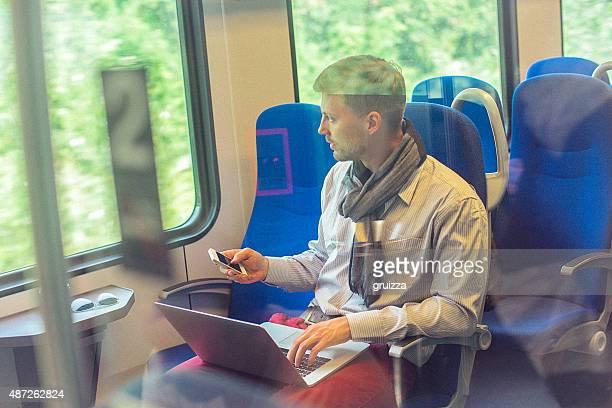 Jeune bel homme travaillant sur ordinateur portable pendant le trajet de travail