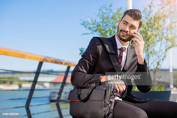 Young handsome manager speaking on his smartphone