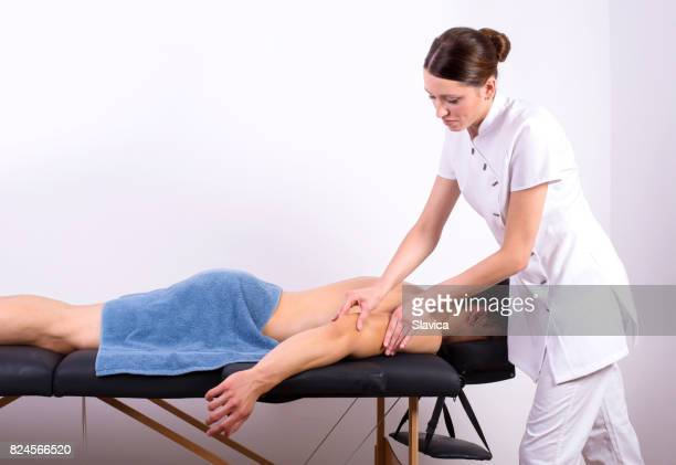young handsome muscular man enjoying back massage in health spa - massage parlour stock photos and pictures
