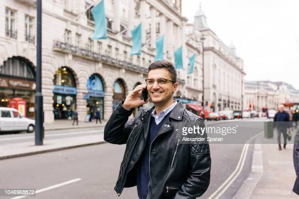 Young handsome smiling man in glasses talking on mobile phone in the street