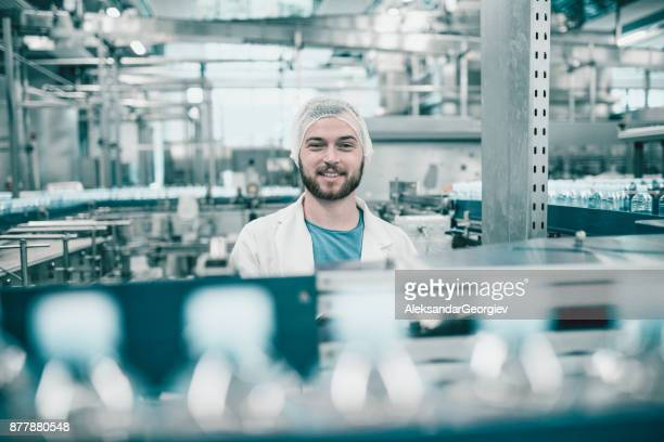 Young Handsome Smiling Scientist With Clipboard Posing in Factory