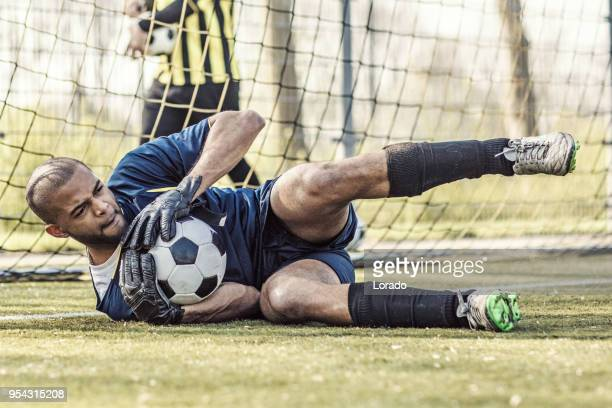 young handsome soccer goalkeeper diving and saving the ball during football training - goalkeeper stock pictures, royalty-free photos & images