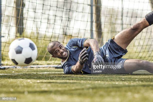 young handsome soccer goalkeeper diving and saving the ball during football training - goalie goalkeeper football soccer keeper stock pictures, royalty-free photos & images