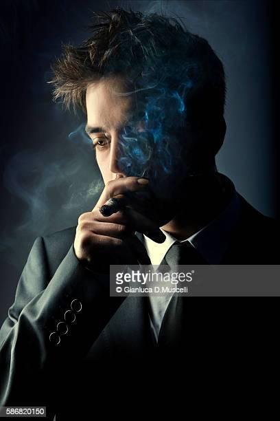 Young handsome stylish man smoking cigar