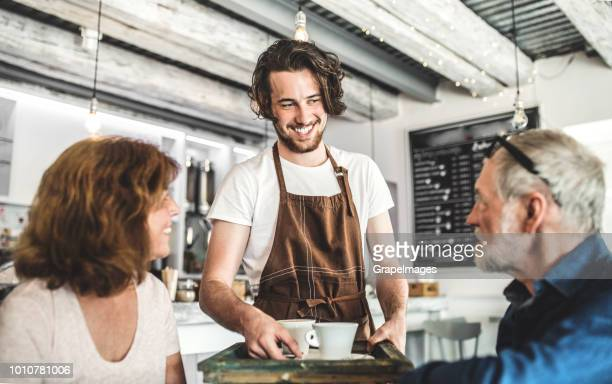 a young handsome waiter bringing coffee to a senior couple in a cafe. - serving food and drinks stock photos and pictures