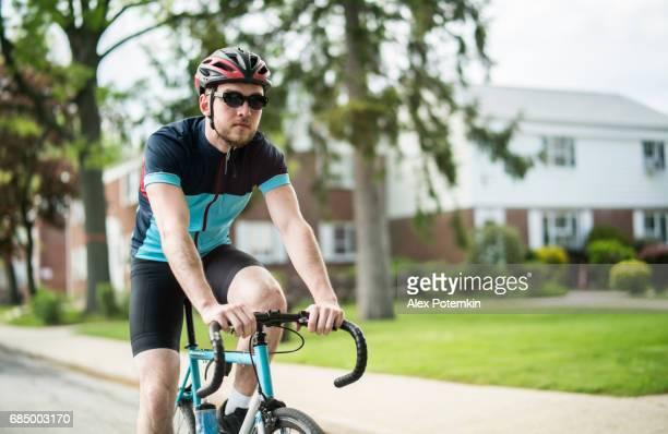 Jonge knappe goed opgeleide man dragen de sportkleding rijden de fiets op de woonstraat in Queens, New York City