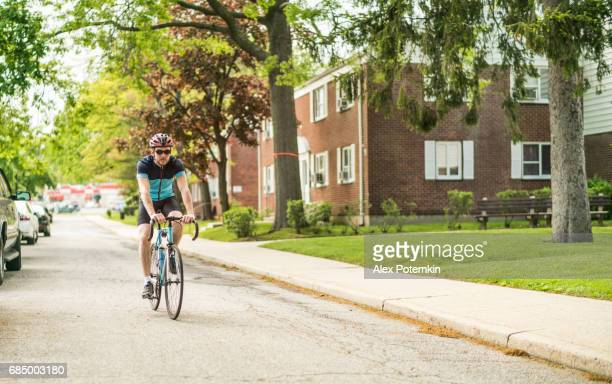young handsome well trained man wearing the sportswear riding the bicycle on the residential street in queens, new york city - queens new york city stock pictures, royalty-free photos & images