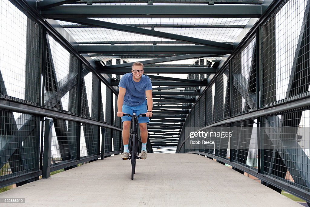 A young, happy adult man riding his bicycle on an urban bridge : Stock Photo
