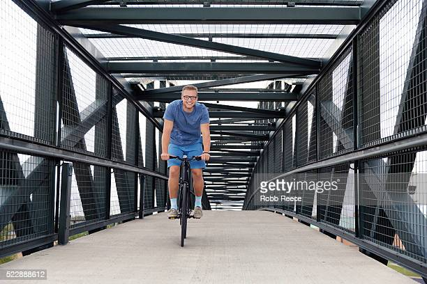 a young, happy adult man riding his bicycle on an urban bridge - robb reece stock-fotos und bilder
